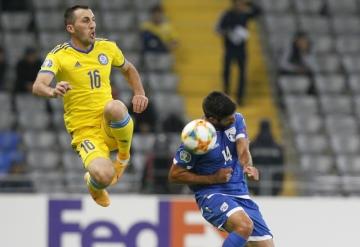Fotbalista Kazachstánu Gafuržan Sujumbajev (vlevo) a  Costas Mintikkis u Kypru v kvalifikačním utkání na ME 2020 hraném 10. října 2019.