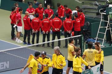 Tým Ekvádoru (dole) se raduje po vítězství nad Japonskem (vzadu) v kvalifikaci na závěrečný turnaj Davisova poháru.