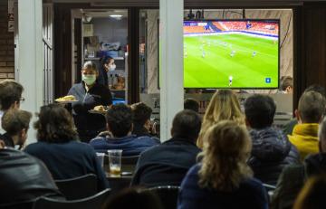 Číšnice ve Valencii obsluhuje 10. března  2020 fanoušky, kteří sledují na televizní obrazovce odvetné osmifinálové utkání Ligy mistrů Valencie - Bergamo.