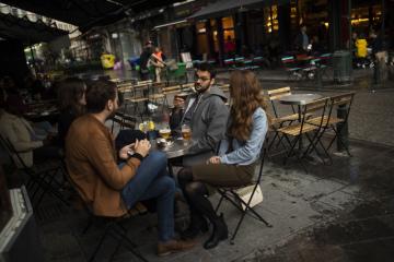 Lidé na zahrádce baru za deštivého večera v Bruselu, 8. června 2020.