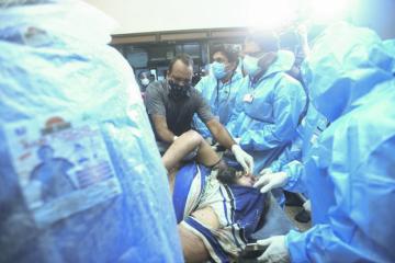 Záchranáři s jednou z osob zraněných po nehodě letadla společnosti Air India (na snímku z 7. srpna 2020).