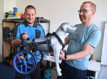 Zakladatelé brněnské společnosti AnyOneGo (zleva) Martin Schenk a Ivan Lukáš pózují 11. srpna 2020 s vozíkem ve své firmě, která vyrábí protetika a invalidní vozíčky pro zvířata. Většinu dílů tiskne na 3D tiskárnách.