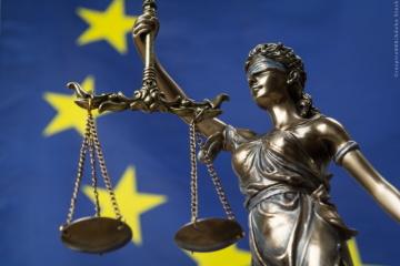 Socha bohyně spravedlnosti Themis nebo Justice se zavázanýma očima, na pozadí vlajka EU