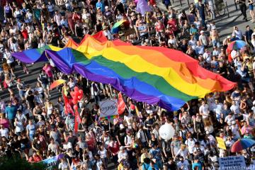 Lidé pochodují s obří duhovou vlajkou před budovou parlamentu v centru Budapešti během průvodu leseb, gayů, bisexuálů a transsexuálů (LGBT) 6. července 2019.(Photo by ATTILA KISBENEDEK / AFP)